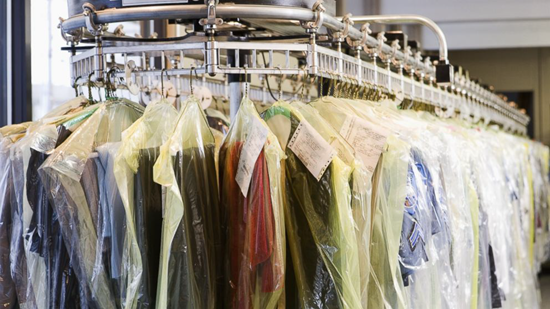 Dry cleaner rack with hanging clothes
